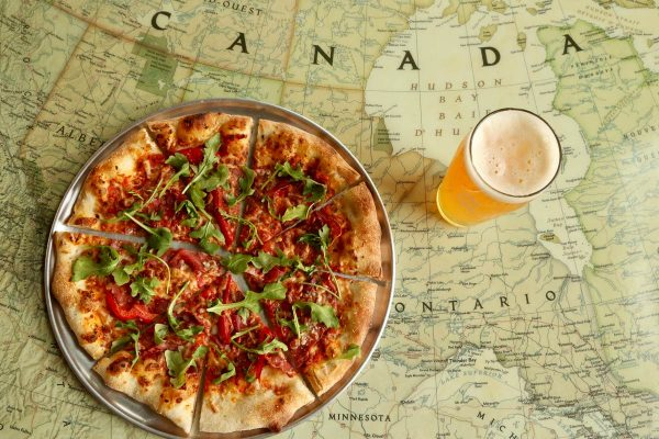 Pizza and beer on top of table top with Canada map