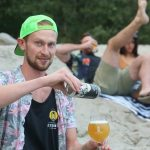Backcountry Brewing | Blew Out My Flip Flop Pina Colada Sour - Man pouring can in glass on a beach